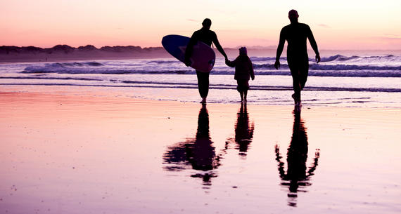 a family walking on the beach at sunset
