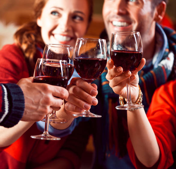 Group of people toasting with glasses of red wine