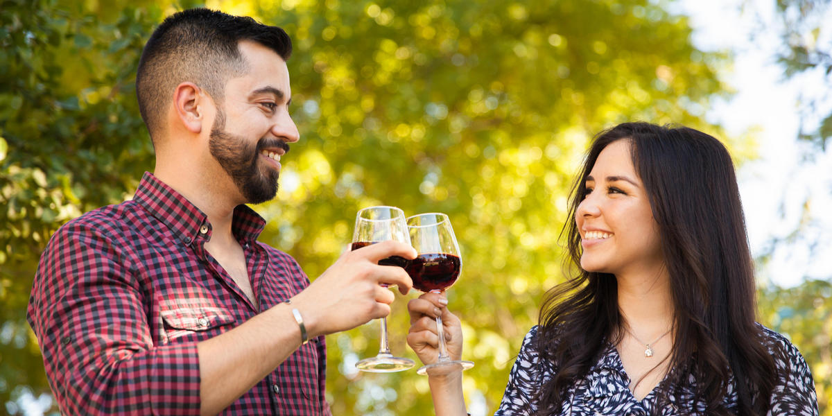 Man and woman toasting glasses of red wine