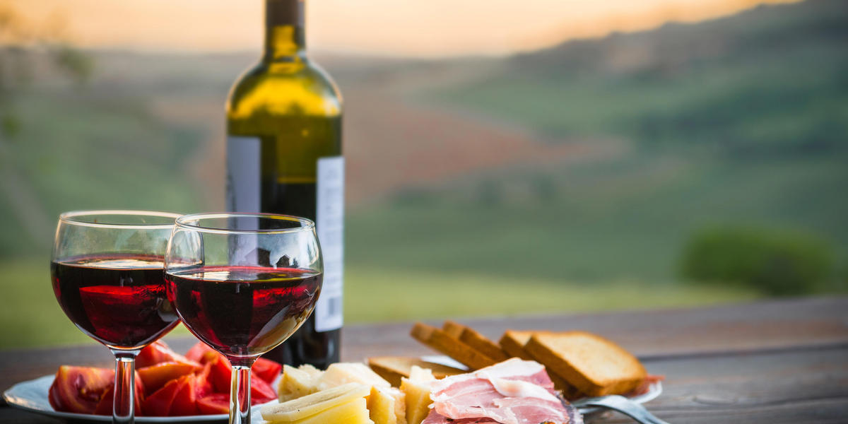 Gourmet picnic of wine, bread, sliced meat, and cheese