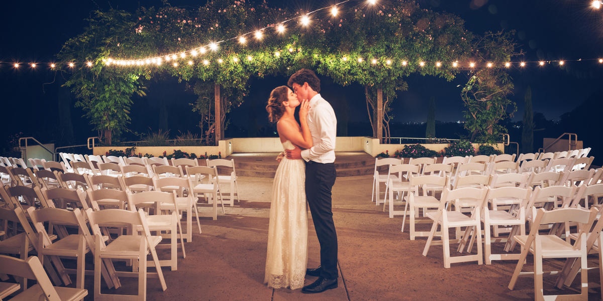 Bride and groom kissing under string lights at night