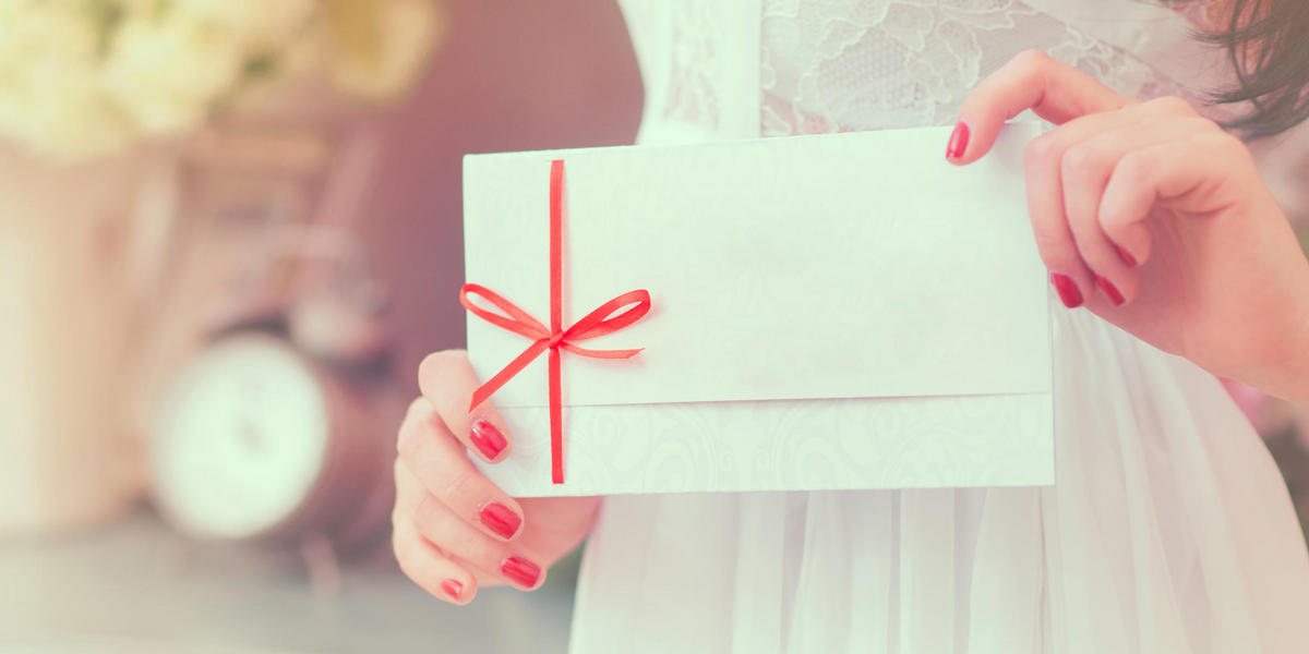 Woman holding an envelope tied with a red bow