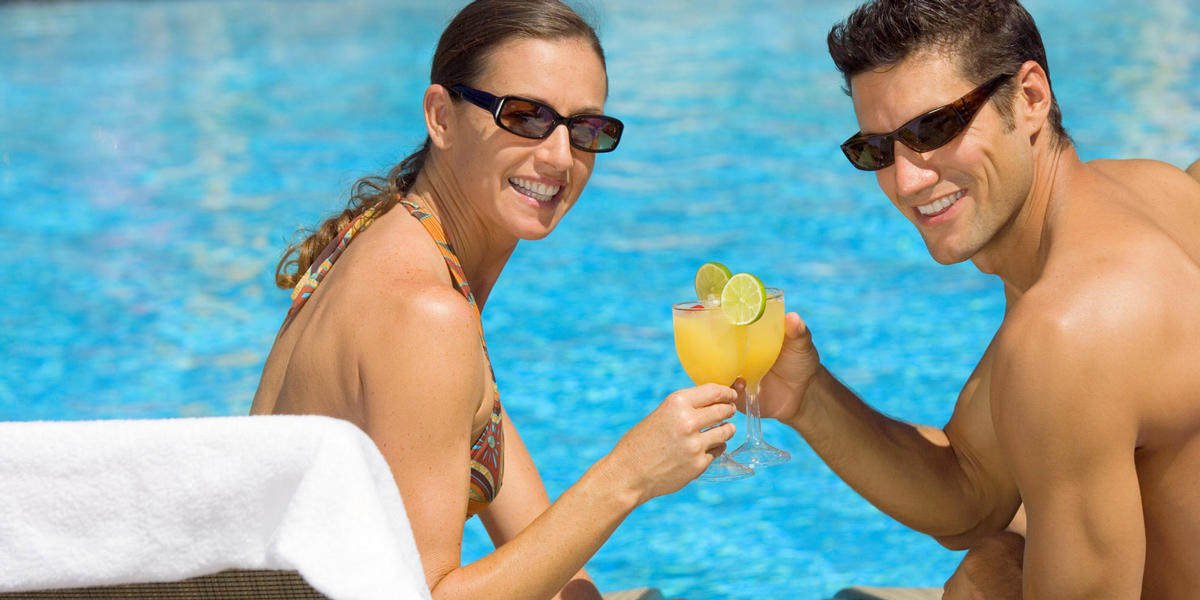 Man and woman enjoying drinks by the pool