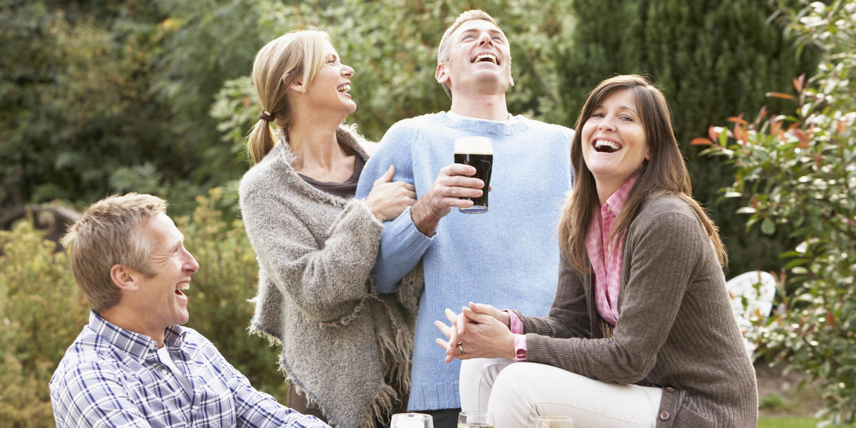 Men and women drinking beer and laughing